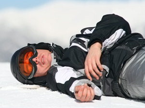 Injured skier laying on the snow.
